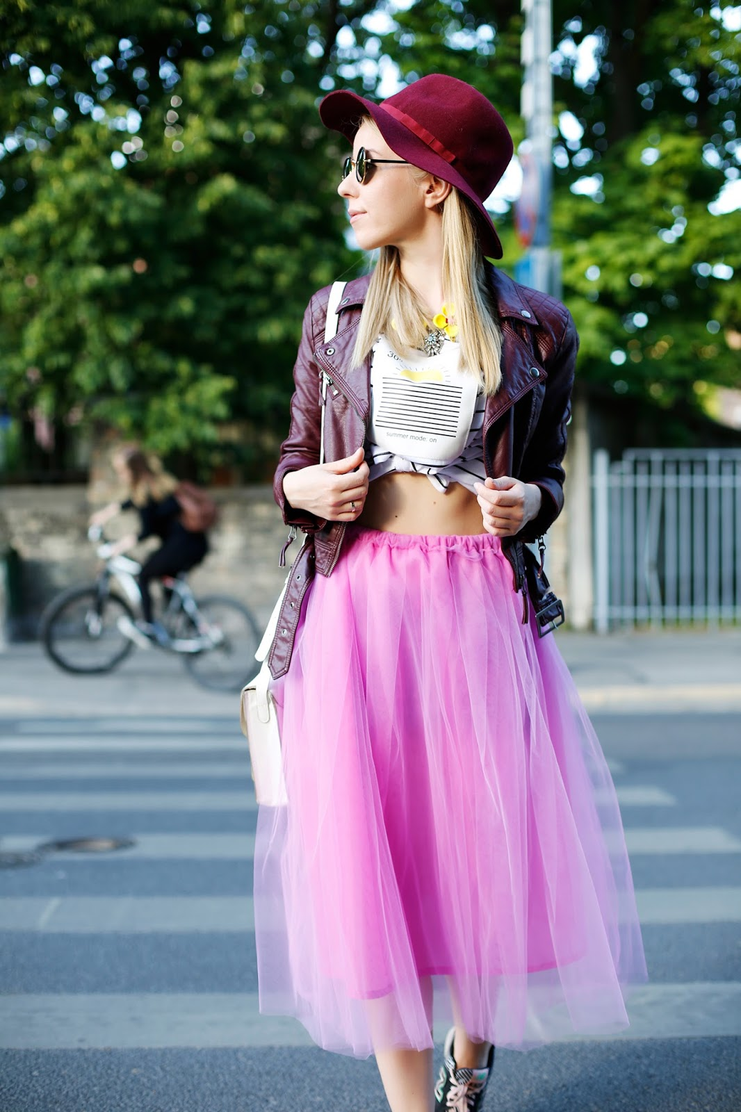 Girl in pink fluffy ballet skirt, sneakers, leather jacket, flippant hat and funny glasses