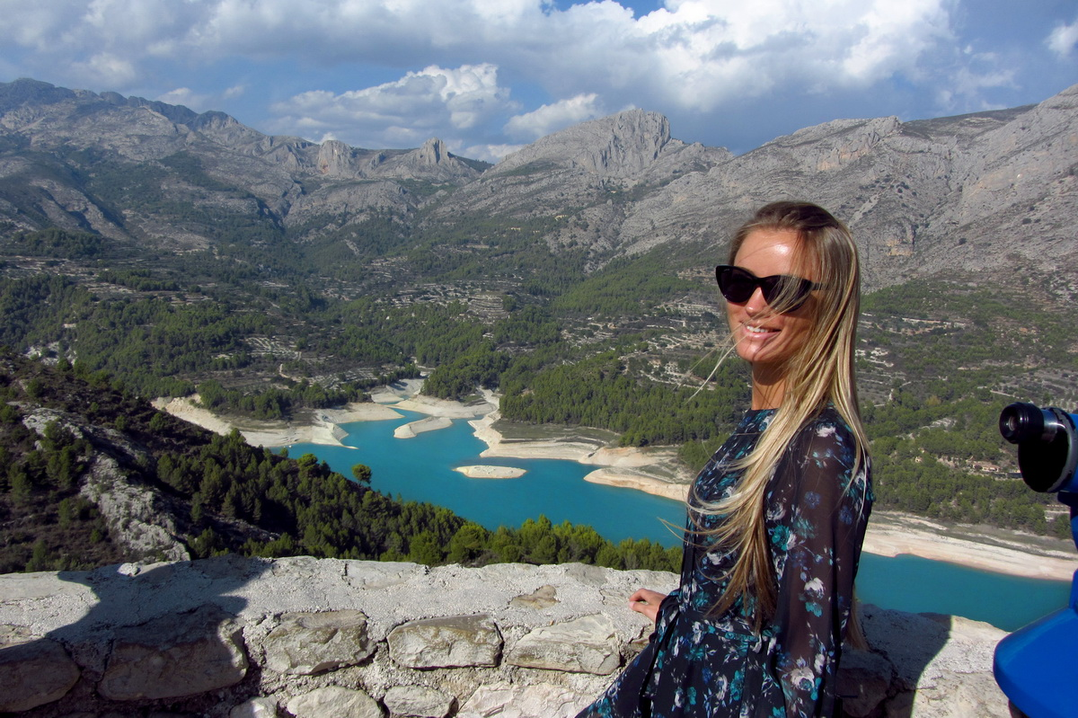 girl smiles looking at beautiful Spain mountains
