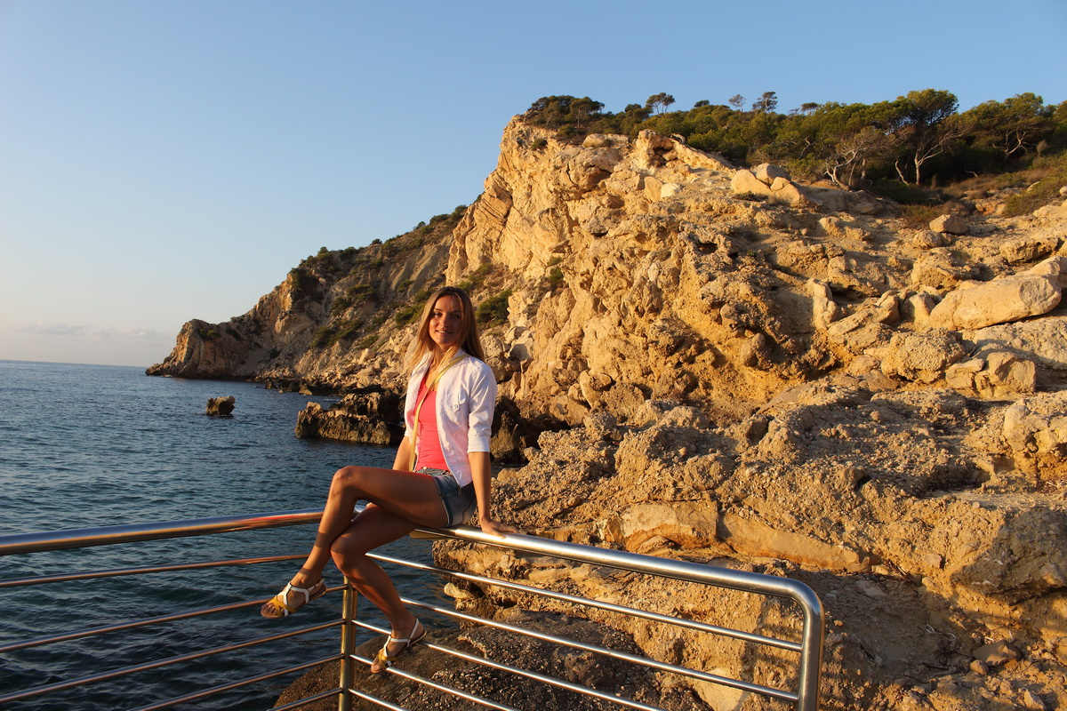 beautiful girl sitting in front of cliff in Spain