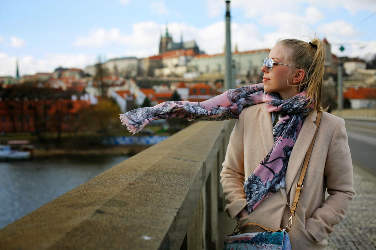 beautiful girl standing on bridge in windy Prague