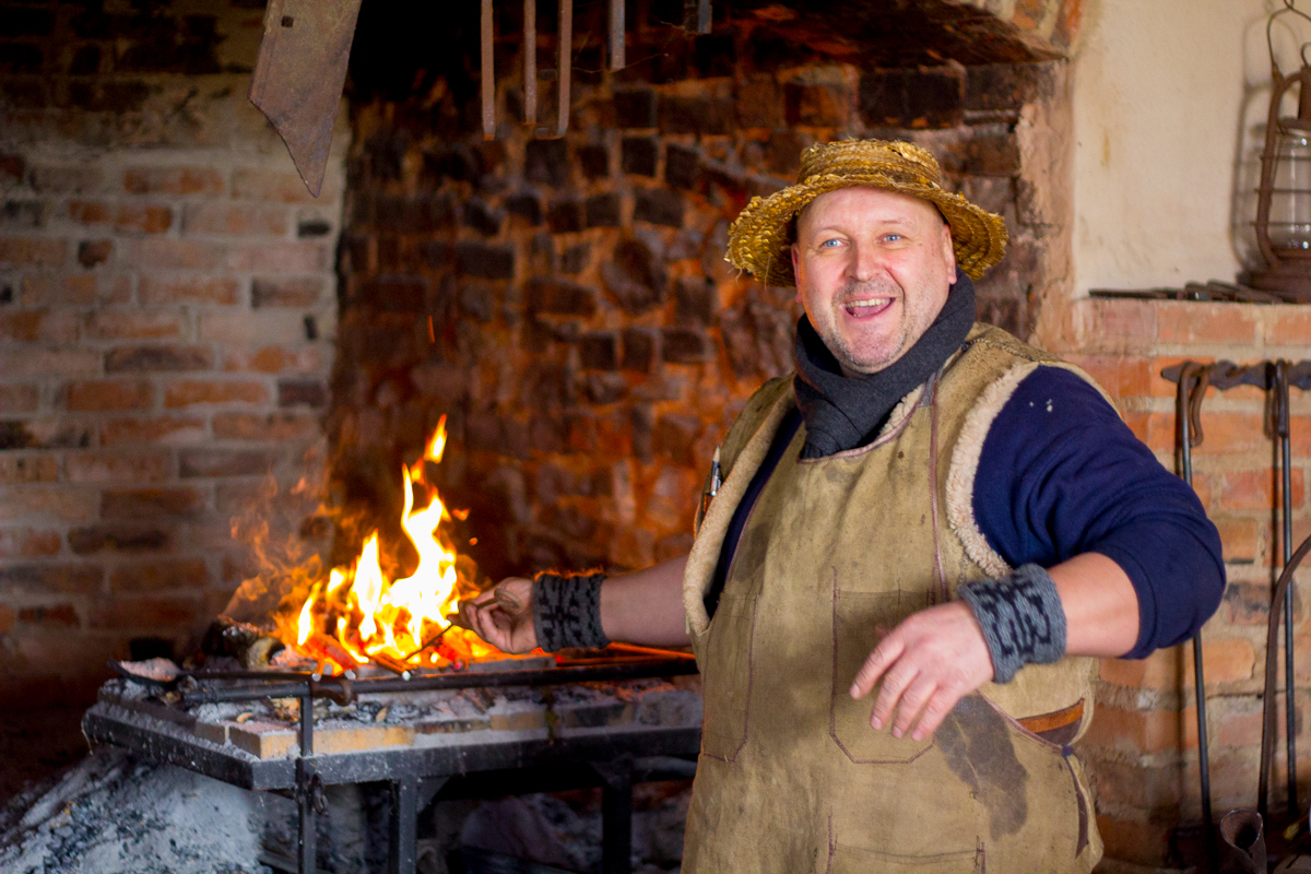 Manor blacksmith at work near the flame