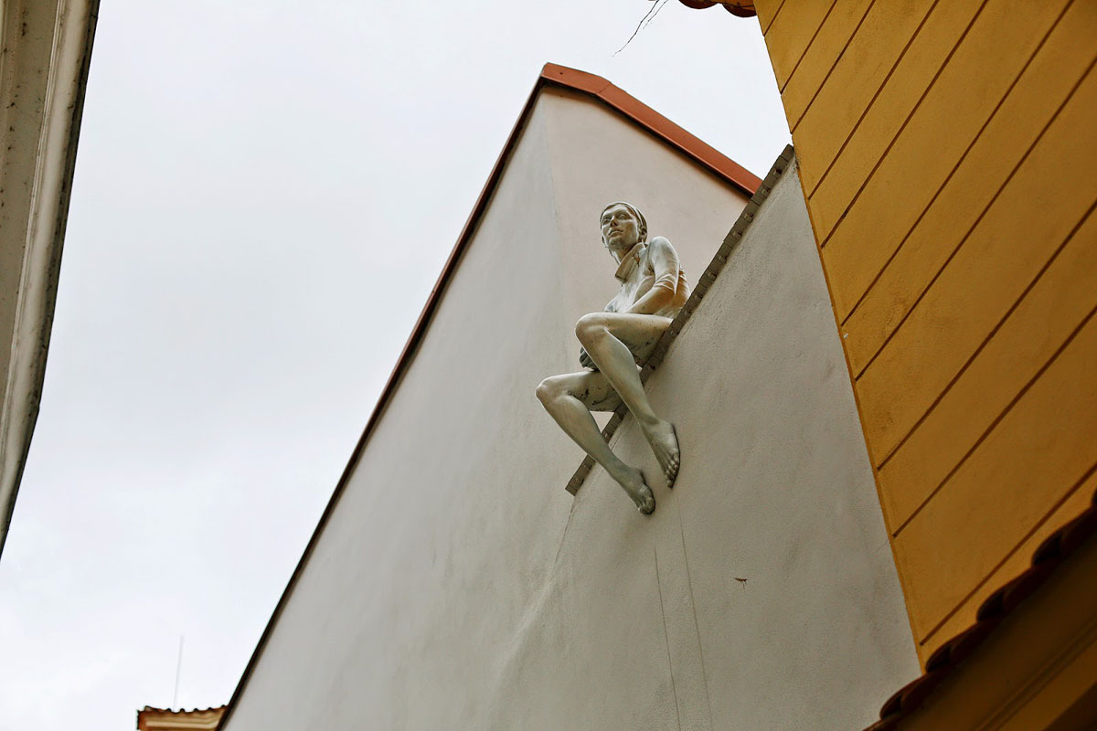 interesting Prague architecture - sculpture of woman sitting on the ledge of wall