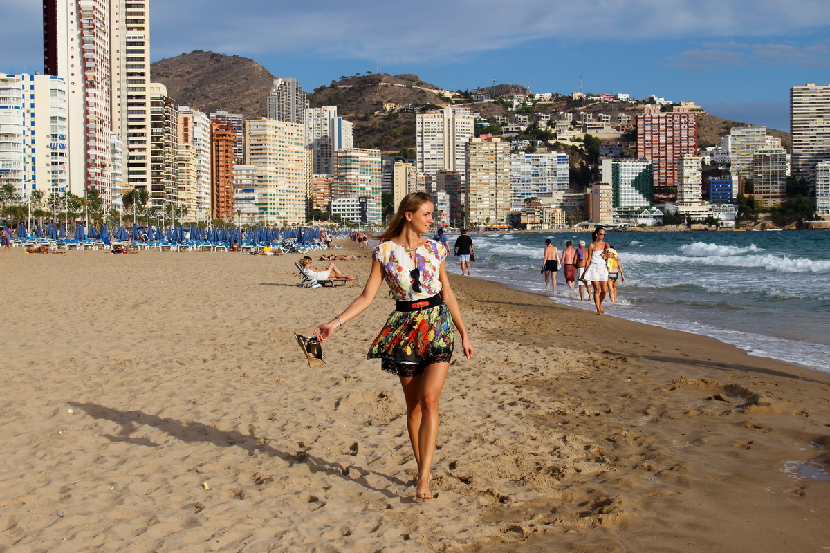 beautiful girl walking down the long sandy beach